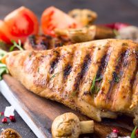 Grilled chicken fillets on wooden board on Gray concrete background. Healthy diet food concept